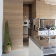 This kitchen's pantry is concealed behind a reflective architecture, countertop, floor, flooring, house, interior design, kitchen, wood, gray, brown