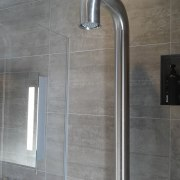 A shower with chunky red handle mixer provides plumbing fixture, shower, tap, gray
