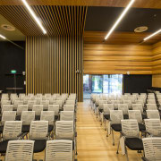 A complex wood design brings visual interest to auditorium, ceiling, conference hall, convention center, function hall, interior design, performing arts center, orange, brown