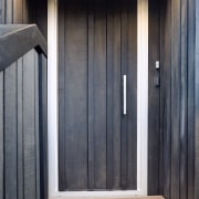 This custom architectural front door melds into the door, floor, hardwood, home, house, wall, window, wood, wood stain, black, gray