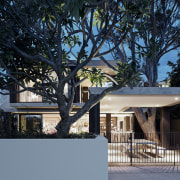 This covered outdoor living areas next to a architecture, building, cottage, estate, facade, home, house, landscape lighting, lighting, property, real estate, residential area, roof, tree, winter, black