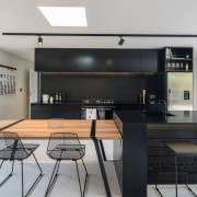 On this project, architect Evelyn McNamara introduced black-stained house, interior design, kitchen, table, gray, black