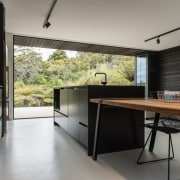 This contemporary black kitchen draws inspiration from the architecture, countertop, house, interior design, real estate, table, gray, black