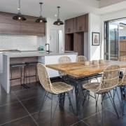 GJ Gardner Taurangas Industrial Rustic show home has countertop, dining room, floor, flooring, hardwood, interior design, kitchen, laminate flooring, real estate, table, wood flooring, gray