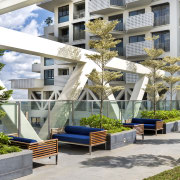 Landscaping and seating on the level 26 sky apartment, architecture, condominium, courtyard, home, mixed use, outdoor structure, plant, property, real estate, residential area, tree, white, gray