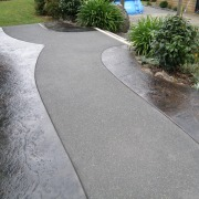 This outdoor area features concrete stamped by Permacolour asphalt, concrete, driveway, flagstone, path, road surface, walkway, gray