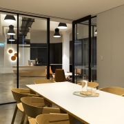 In this office fit-out, ceiling-height sliding doors combine dining room, furniture, interior design, room, table, brown, orange