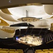The auditorium at the Philharmonie de Paris was architecture, auditorium, ceiling, light, lighting, performing arts center, theatre, tourist attraction, yellow, brown
