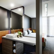 Guest bedrooms and bathrooms are open-plan to optimise ceiling, interior design, room, suite, white, black, gray
