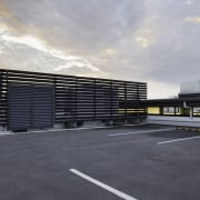 Plant-screening louvres at NorthWest Shopping Centre contribute to architecture, asphalt, building, commercial building, corporate headquarters, facade, headquarters, line, parking, parking lot, sky, gray