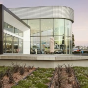This dramatic curving showroom facade is created in architecture, building, home, house, mixed use, real estate, gray, brown