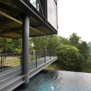 A walkway traverses the site beneath this house, architecture, house, property, real estate, reflection, swimming pool, water, black, white