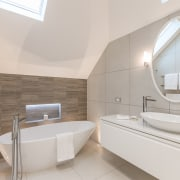 An angular, asymmetrical ceiling is echoed in the architecture, bathroom, floor, home, interior design, plumbing fixture, product design, room, sink, tap, toilet seat, gray