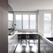 This galley-style kitchen has close work triangles and architecture, countertop, daylighting, floor, house, interior design, kitchen, product design, room, table, window, gray, white