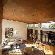 The predominant use of wood on the double-height architecture, ceiling, daylighting, home, house, interior design, living room, real estate, room, table, wood, brown
