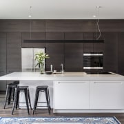 A cantilevered countertop end with four stools tucked cabinetry, countertop, cuisine classique, interior design, kitchen, gray, black