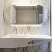 In this design, a richly veined marble feature bathroom, bathroom accessory, bathroom cabinet, bathroom sink, furniture, interior design, plumbing fixture, product, product design, sink, tap, gray
