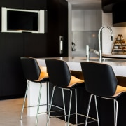 On this island, the benchtop protrudes out past chair, countertop, floor, flooring, furniture, interior design, kitchen, product design, table, black, gray