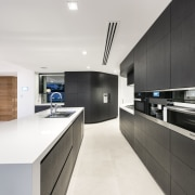On this project by Hillam Architects, push-to-open handles architecture, countertop, interior design, kitchen, product design, real estate, white, black