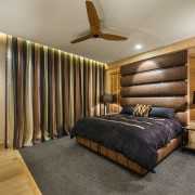 The headboard in this lavish guest bedroom echoes bed frame, bedroom, ceiling, interior design, real estate, room, suite, wood, gray, brown