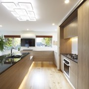 This glamorous contemporary kitchen was installed by Markov ceiling, countertop, daylighting, floor, flooring, hardwood, house, interior design, kitchen, laminate flooring, living room, real estate, wood, wood flooring, gray