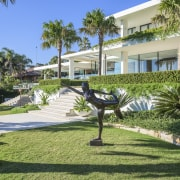 Artwork graces the front lawn of this six-level apartment, arecales, condominium, cottage, estate, grass, hacienda, home, house, landscaping, lawn, leisure, neighbourhood, palm tree, plant, property, real estate, residential area, resort, tree, villa, walkway, green