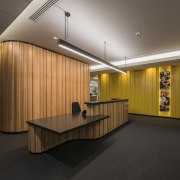The wood-finished pod behind the reception desk on architecture, ceiling, interior design, lobby, product design, black, brown
