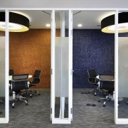 In the AMGeneral fit-out, private booths on the ceiling, floor, flooring, glass, interior design, light fixture, lighting, structure, wall, gray