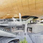 Lower level retail provides direct access to the architecture, building, convention center, corporate headquarters, daylighting, daytime, headquarters, line, metropolis, metropolitan area, mixed use, sport venue, structure, urban area, orange, gray