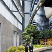 Ground floor lobby space next to the hotel architecture, building, condominium, metropolitan area, mixed use, plant, tourist attraction, tree, gray