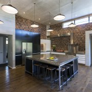 Brick-look panelling, black and white cabinetry, a concrete ceiling, floor, flooring, hardwood, house, interior design, loft, real estate, wood flooring, gray