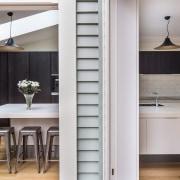 A long cantilevered Corian island benchtop doubles as cabinetry, countertop, cuisine classique, floor, flooring, furniture, interior design, kitchen, gray