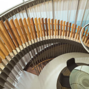 A spiral staircase looks down on the dining stairs, brown