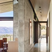 Concrete is the predominant interior material in this architecture, ceiling, daylighting, floor, flooring, house, interior design, lobby, real estate, wall, wood flooring, gray