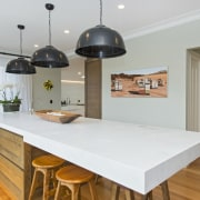 A chunky island countertop is a feature of ceiling, countertop, floor, flooring, hardwood, home, interior design, kitchen, property, real estate, room, table, wood flooring, gray, white