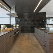 Black ceramic tiles create a feature wall in cabinetry, countertop, interior design, kitchen, real estate, brown, gray