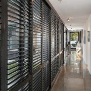 Operable shutters lining the circulation corridor control the interior design, real estate, gray, black
