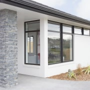 A schist-clad pillar provides an attractive entry feature door, facade, home, house, property, real estate, siding, window, white, gray