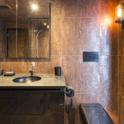 Even the black wall-hung toilet is a sculptural bathroom, cabinetry, ceiling, countertop, floor, flooring, interior design, lighting, room, tile, wall, wood flooring, brown