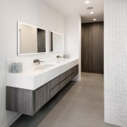 The vanity is tucked to the side of bathroom, bathroom accessory, bathroom cabinet, floor, flooring, interior design, product design, room, sink, tile, wall, white
