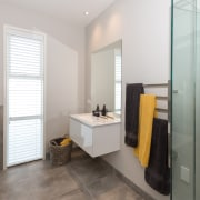 This family bathroom has a vanity with a bathroom, bathroom accessory, bathroom cabinet, floor, interior design, real estate, room, gray