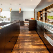 In this clean-lined kitchen, a Smeg rangehood is countertop, interior design, kitchen, real estate, wood, brown, white