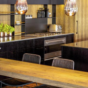 A sleek Smeg oven and cooktop were chosen furniture, interior design, restaurant, table, wood, orange, black