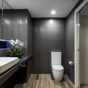 Contrasting a grey-black palette, a veneer vanity top bathroom, interior design, plumbing fixture, product design, public toilet, room, toilet, gray, black
