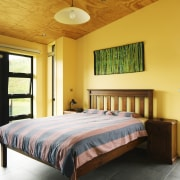 Plywood ceilings in this bedroom are complemented by bed, bed frame, bedroom, ceiling, estate, furniture, home, interior design, property, real estate, room, wood, orange