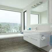 This coastal residences two bathrooms are both trained bathroom, bathroom accessory, estate, floor, home, interior design, property, real estate, room, window, white, gray