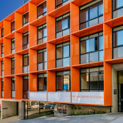 The Orange apartments feature a distinctive vibrant facade apartment, architecture, building, city, commercial building, condominium, corporate headquarters, elevation, facade, home, house, metropolitan area, mixed use, neighbourhood, real estate, residential area, tower block, urban area, window, red