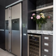 A discreet wall separates the wine fridge and home appliance, kitchen, major appliance, refrigerator, black, gray