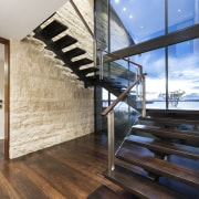 The wooden staircase matches the wooden floors on architecture, daylighting, floor, flooring, glass, handrail, hardwood, home, house, interior design, real estate, stairs, window, wood, wood flooring, black