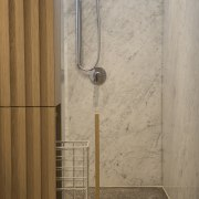In this bathroom by designer Leon House, a plumbing fixture, shower, tile, wall, brown, gray